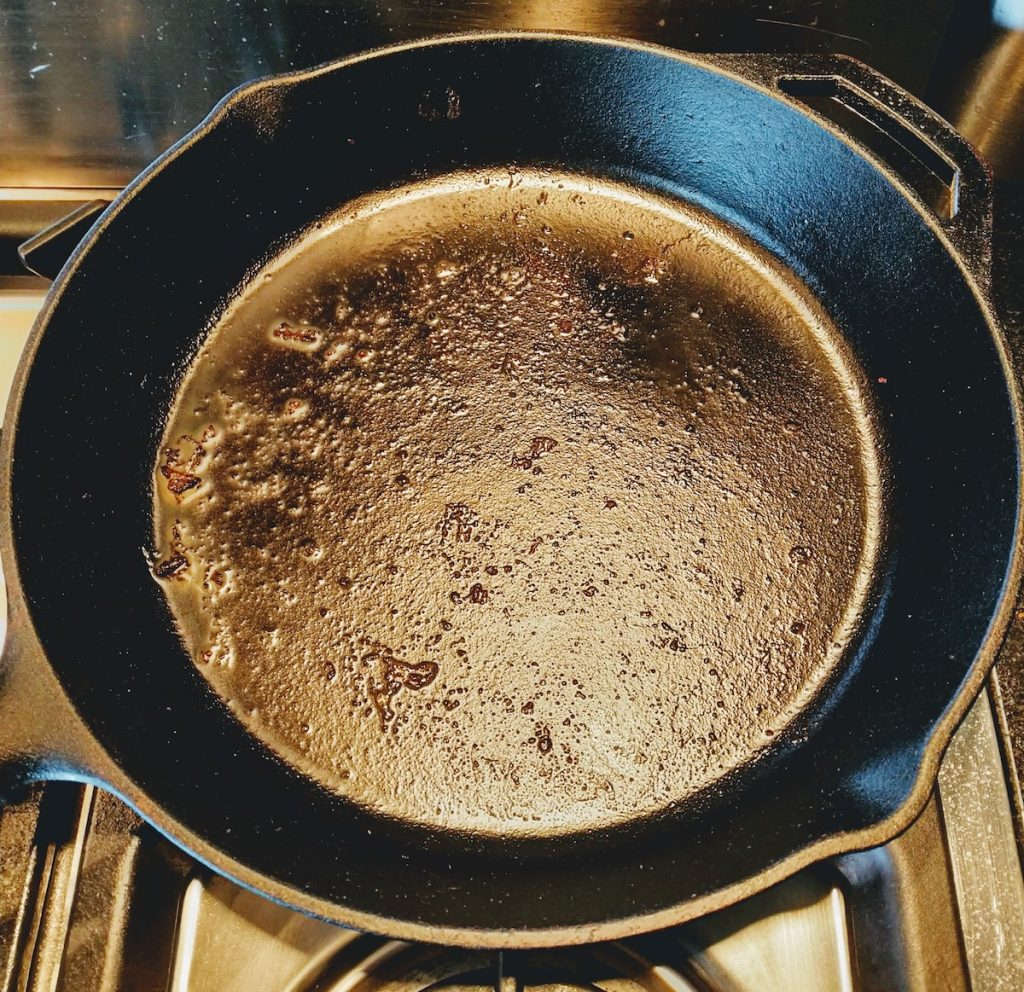 Picture of a cast iron pan with stuck on meat before cleaning.