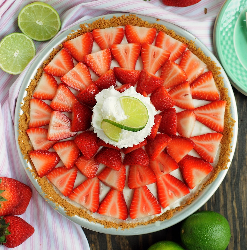 Picture of a cheesecake on a table with lime and strawberry