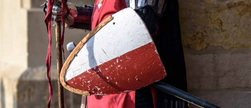 Soldier holding a red and white/grey shield