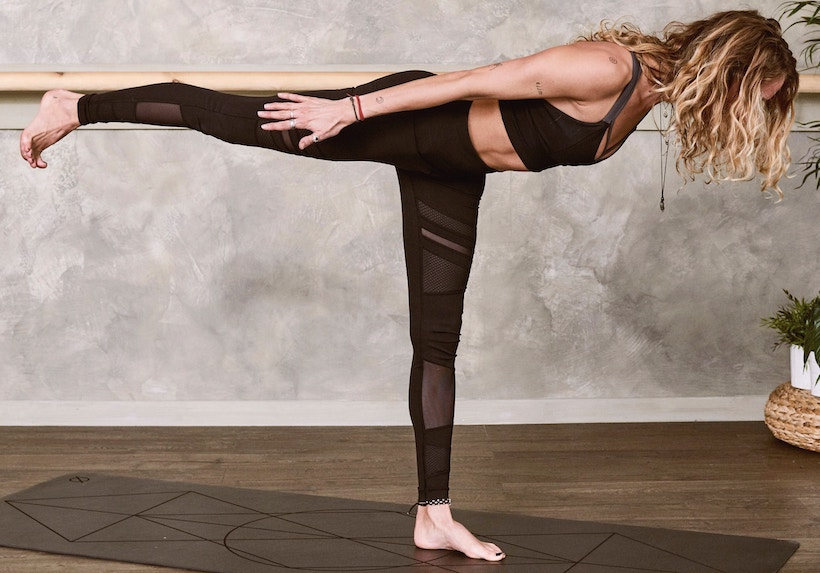 Lady on one leg in yoga post on mat