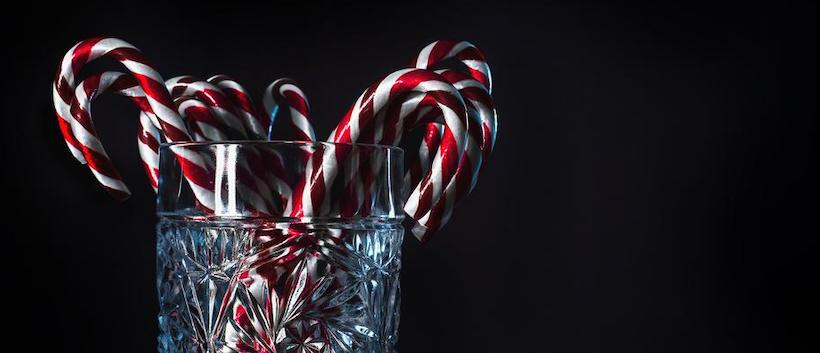 Crystal glass holding large candy canes 1/3s of image
