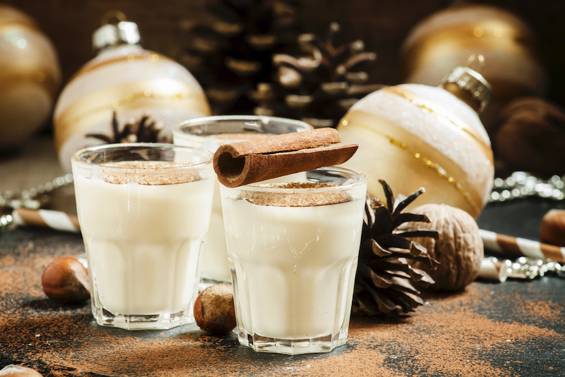 Eggnog with milk, cinnamon, grated nutmeg, decorated with fir cones, beads, nuts and Christmas balls, selective focus