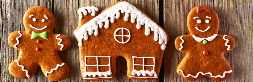 Christmas homemade gingerbread couple and house on wooden table
