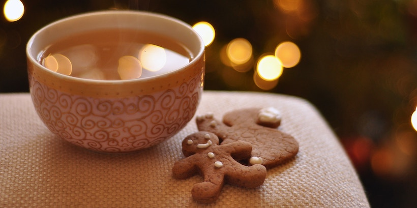 Cider cup next to gingerbread cookies with lights bokeh in back