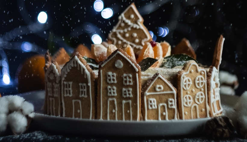 Gingerbread village with tree centerpiece and lights in back
