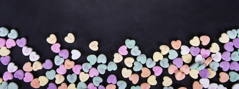 Conversation hearts on a black chalkboard background.