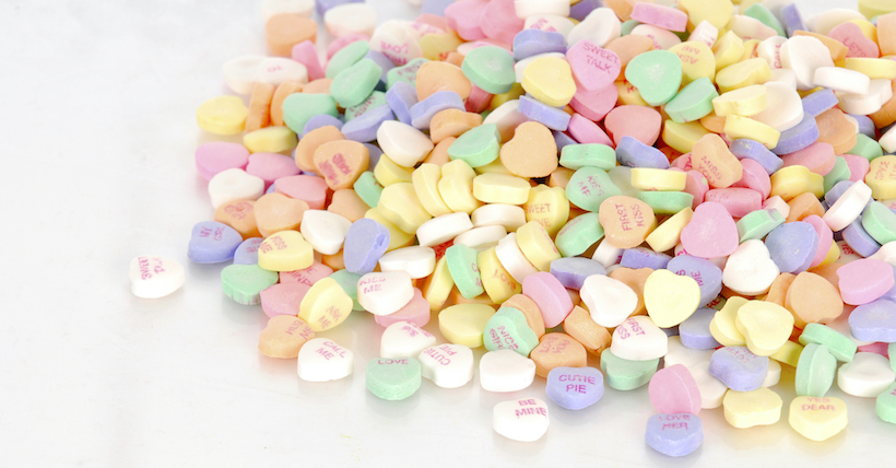 pile of candy hearts with reflection on white background