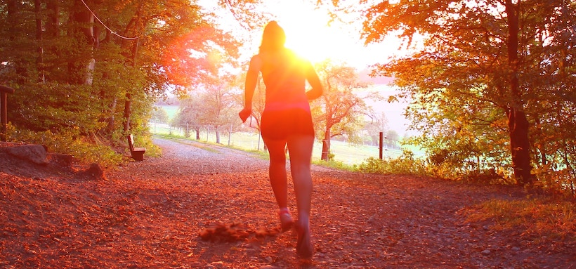 Runner from the back with sun streaming at sunset