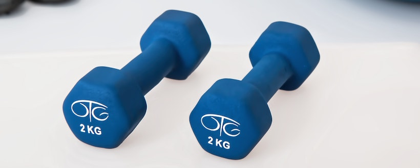 Small blue dumbbells on a white floor