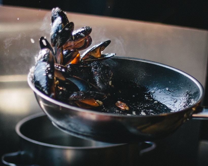 Clams being tossed in a black pan