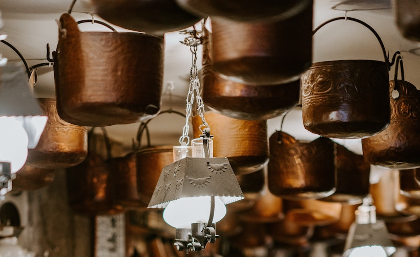 Copper cookware hanging from ceiling in kitchen