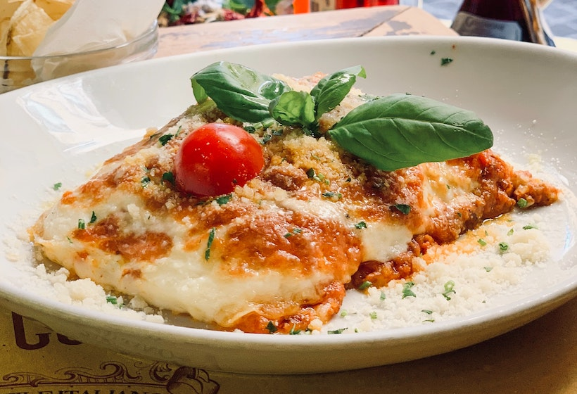 Lasagna on a ceramic plate with tomato and basil