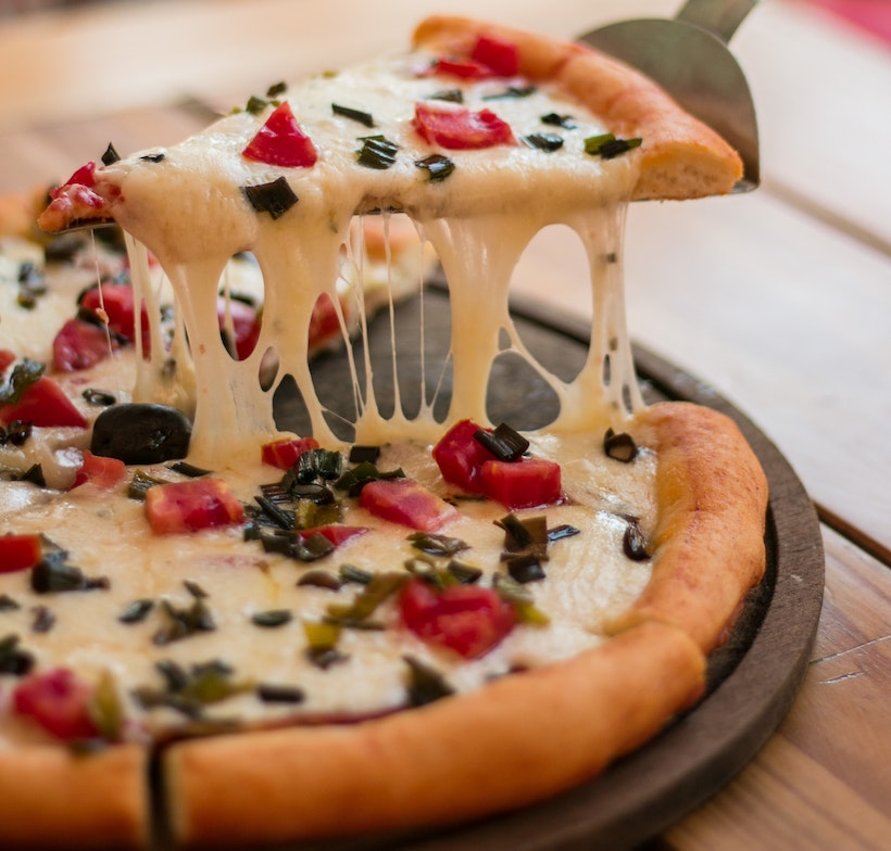 Pizza lifted showing stringy cheese connecting to pie