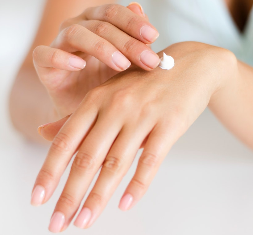 Lady applying lotion to rub into her hands