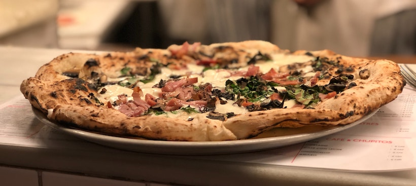 Pizza with ham and greens on a pizza menu
