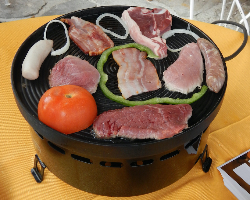 Round raclette grill with meat and vegetables