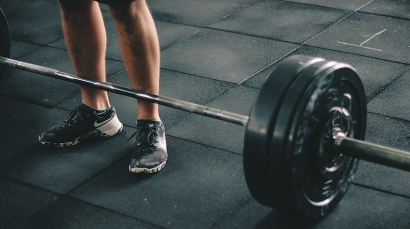 A man prepares to deadlift a barbell