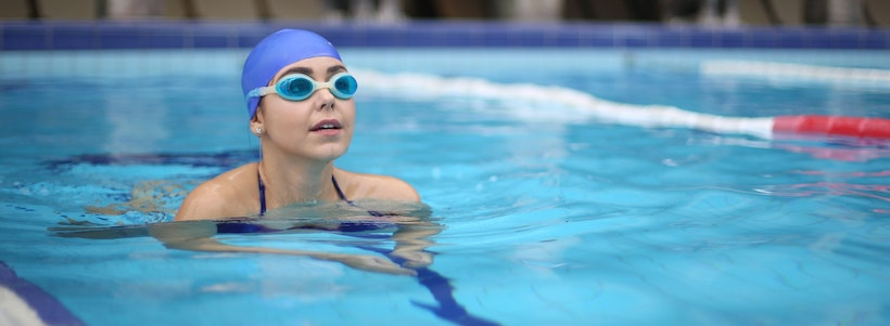 Woman in the pool wearing goggles