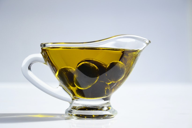 Pitcher with olive oil and olives inside