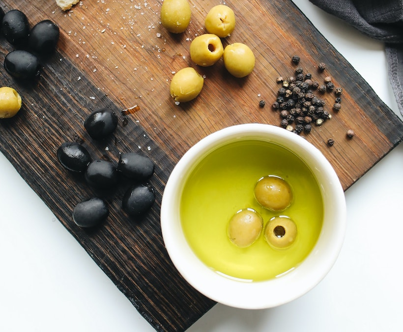 Olives, peppercorns, and olive oil on a cutting baord