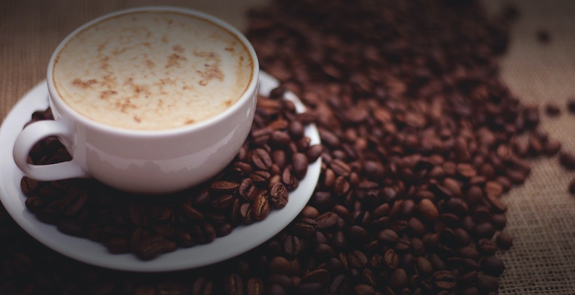 Coffee cup with milk next to whole coffee beans