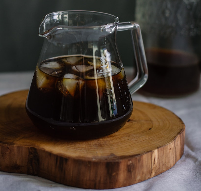 Glass pitcher with ice and coffee