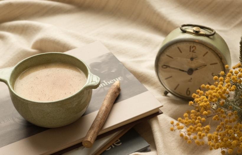 Chai tea on a book next to an alarm clock