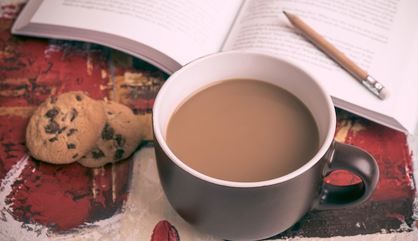 Cookies, coffee with milk, and a pencil on a book