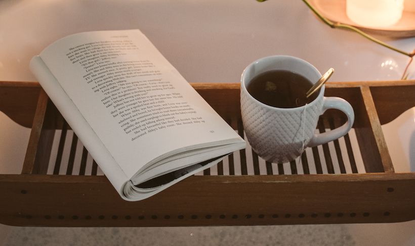 Cup of tea and an open book held over a tub with a candle