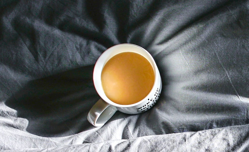 A coffee mug with creamer sitting on grey sheets
