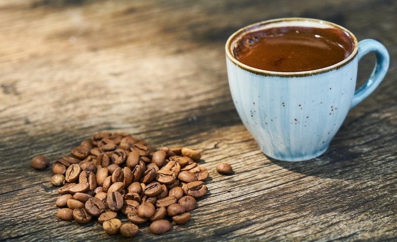 Coffee cup next to coffee beans on wooden table