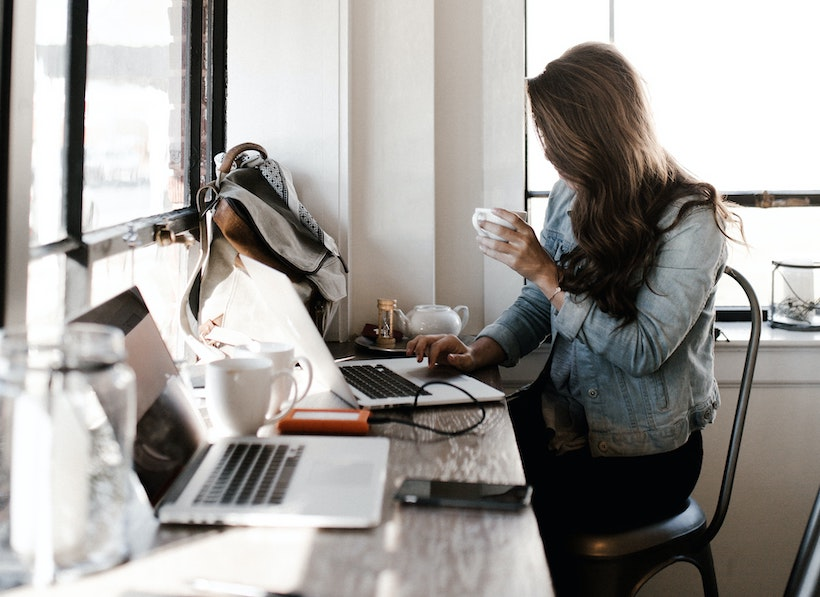 Lady in a grey and blue jacket holds coffee while working on a laptop