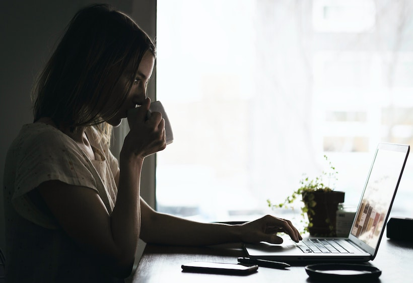 A lady drinks coffee while scrolling on a computer