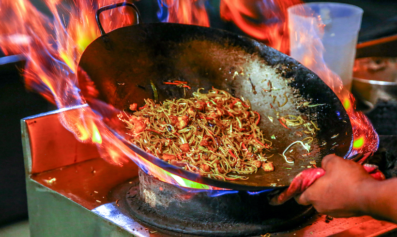 Lots of flame in a wok on an open burner with noodles