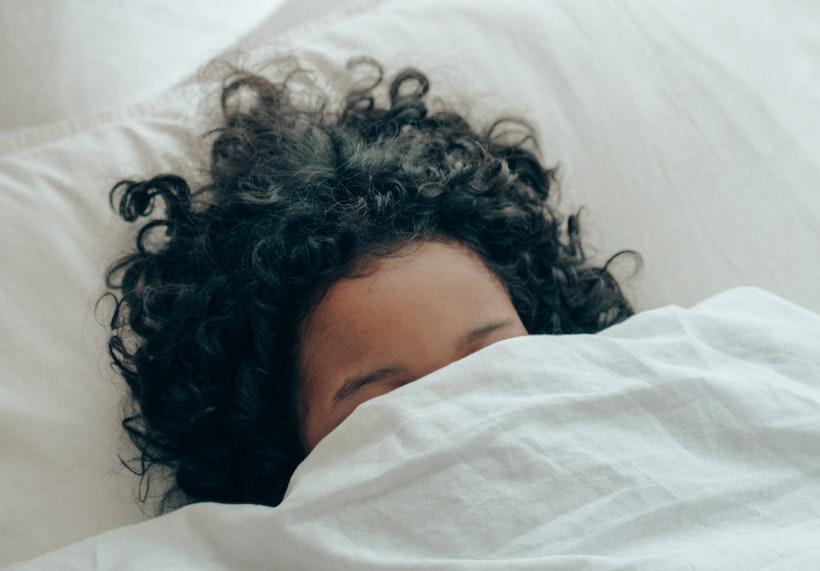 A woman naps under a blanket