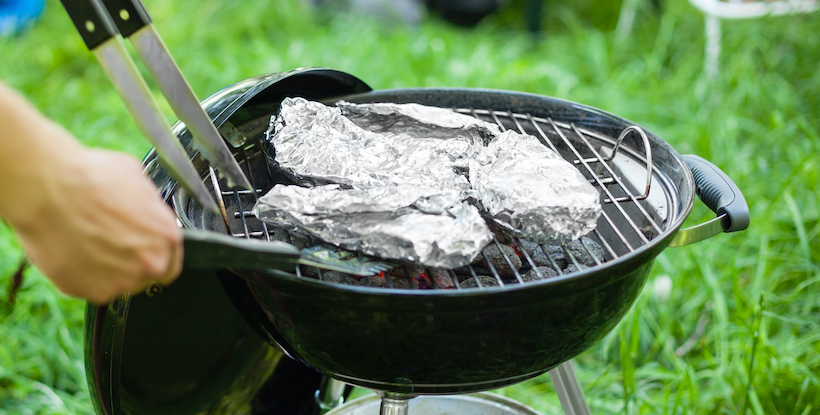 Grilling meat with barbecue an tin foil and tongs. Horizontal close up shot with a selective focus