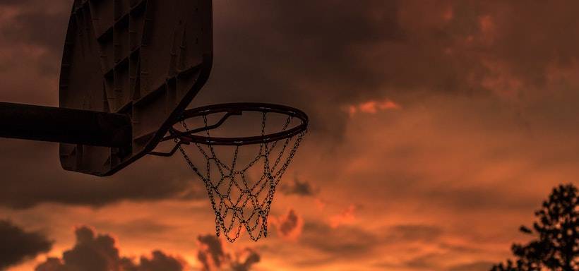 Ominous orange sky behind basketball hoop