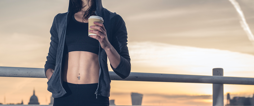 An athletic young woman with toned abs and coffee cup in hand