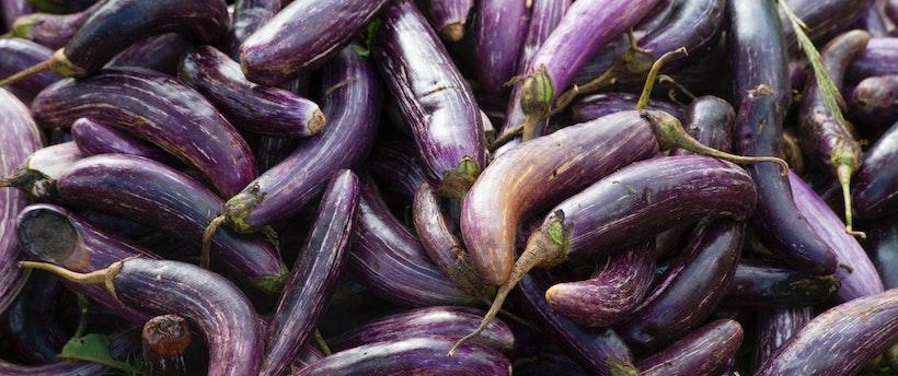 A large bunch of purple eggplants