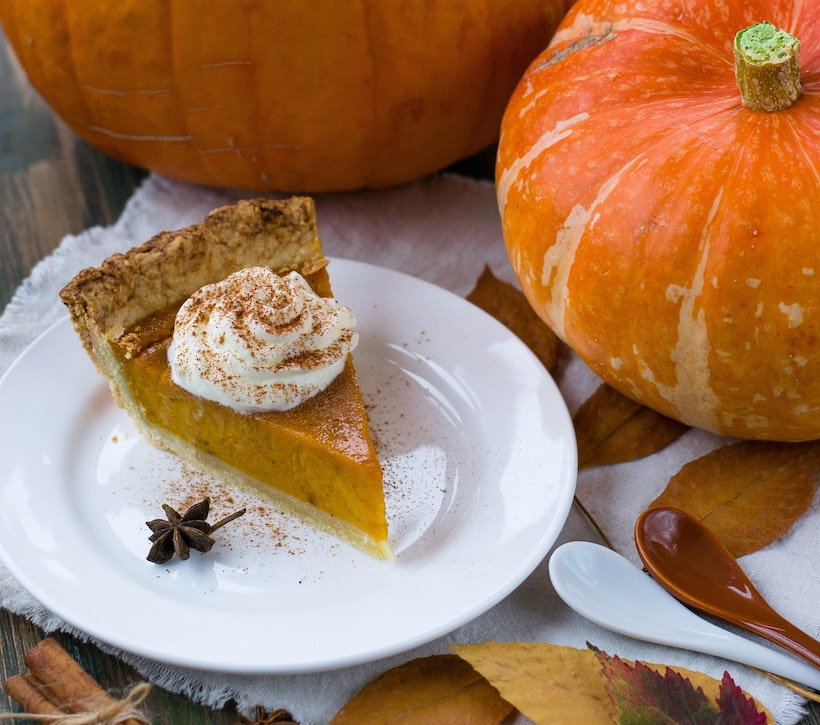 Pumpkin pie with cream and spice next to a pumpkin