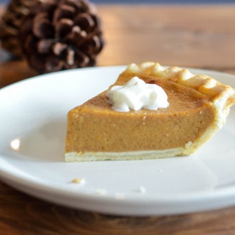 Pumpkin pie slice in front of pinecones