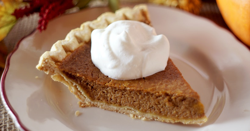 Close up shot of a slice of pumpkin pie on a ceramic plate