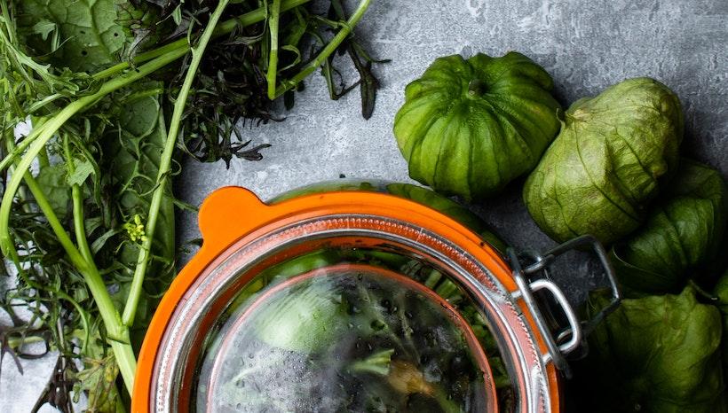 Tomatillos and greens near a pot