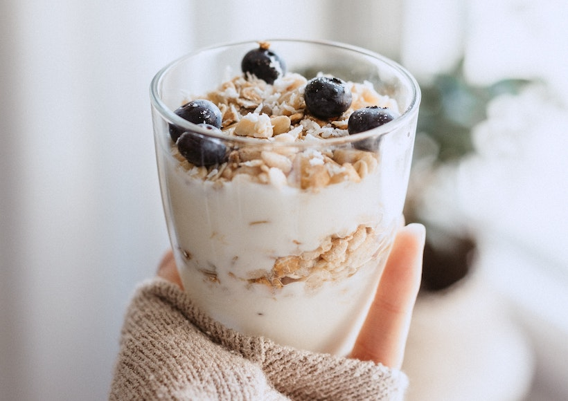 Lady holding a cup of yogurt with granola and blueberries