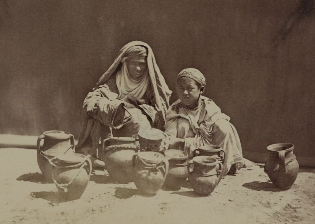 An older lady and young boy with jugs likely containing yogurt