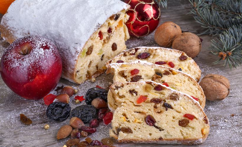 Stollen like fruitcake cut open with powdered sugar and dried fruit