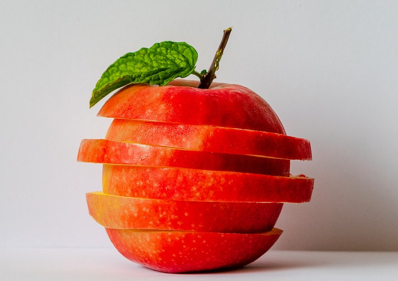 An apple in slices stacked to look like a whole