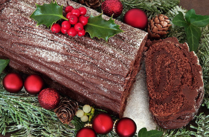 Chocolate yule log cake with red bauble decorations, holly, ivy, and mistletoe