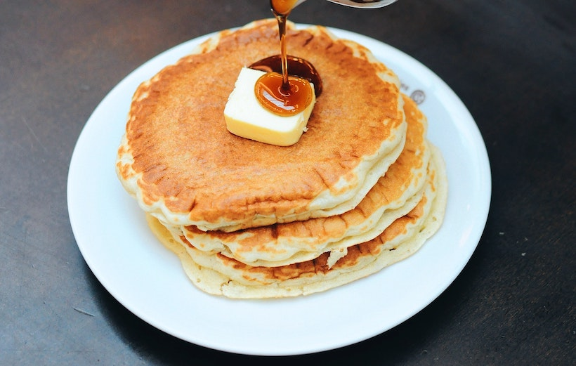 Pancakes on a plate with butter on top and poured syrup