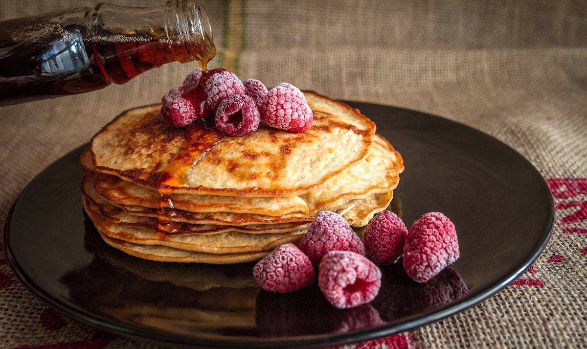 Thinner crepe style pancakes with syrup and raspberries